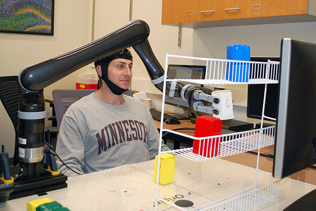 Research subjects at the University of Minnesota fitted with a specialized noninvasive EEG brain cap were able to move a robotic arm in three dimensions just by imagining moving their own arms (credit: University of Minnesota College of Science and Engineering)
